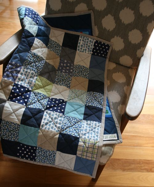 Folded quilt with cross stitch label